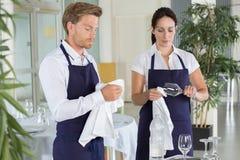 Vidros de limpeza da empregada de mesa e do garçom no restaurante Fotos de Stock Royalty Free