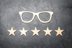 Vidros de madeira e cinco estrelas em um fundo concreto Vidros de alta qualidade O melhor sistema ótico Correção da visão foto de stock royalty free