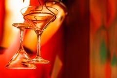 Vidros de Martini que penduram com fundo vermelho Fotos de Stock