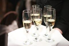 Vidros de oferecimento do empregado de mesa de Champagne na bandeja Fotos de Stock
