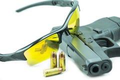 Vidros de sol alaranjados e pistola preta da arma de 9mm isolada no fundo branco Foto de Stock