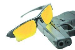 Vidros de sol alaranjados e pistola preta da arma de 9mm isolada no fundo branco Fotografia de Stock Royalty Free