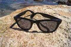 Vidros de Sun nas rochas Fotografia de Stock