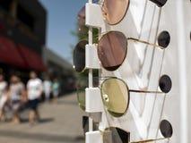 Vidros de Sun no contador três pares de óculos de sol em cores diferentes imagens de stock royalty free