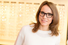 Vidros de tentativa da mulher atrativa nova no ótico foto de stock royalty free