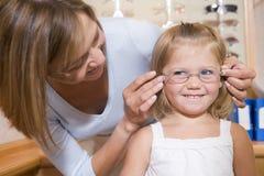 Vidros de tentativa da mulher na rapariga em optometrists Imagem de Stock Royalty Free