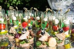 Vidros de vidro Os vidros são enchidos com os petiscos: tomate de cereja, mussarela Foto de Stock Royalty Free