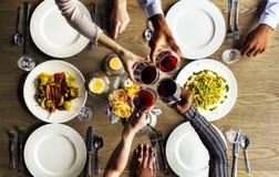 Vidros de vinho aderindo-se dos povos junto no restaurante foto de stock royalty free