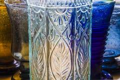 Vidros de vinho coloridos e uma garrafa Imagens de Stock