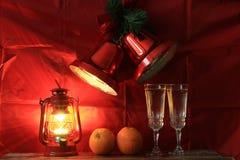 Vidros de vinho com champanhe e uma lâmpada decorativa em um fundo vermelho Fotos de Stock
