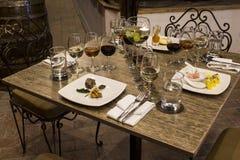 Vidros de vinho com guardanapo, vidros e alimento gourmet, tabela de banquete Imagens de Stock