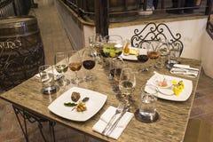 Vidros de vinho com guardanapo, vidros e alimento gourmet, tabela de banquete Fotos de Stock
