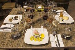 Vidros de vinho com guardanapo, vidros e alimento gourmet, tabela de banquete Imagem de Stock