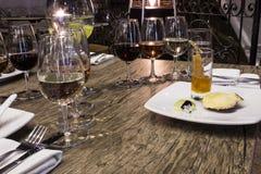 Vidros de vinho com guardanapo, vidros e alimento gourmet, tabela de banquete Fotos de Stock Royalty Free