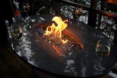 Vidros de vinho em torno do fogo Fotos de Stock Royalty Free