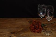 Vidros de vinho gravados bonitos com uma única rosa vermelha na tabela de madeira e no fundo escuro fotografia de stock