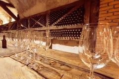 Vidros de vinho na tabela de madeira da sala de gosto da adega velha Fotografia de Stock Royalty Free