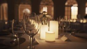 Vidros de vinho vazios na tabela com velas e as placas leves no salão do banquette vídeos de arquivo