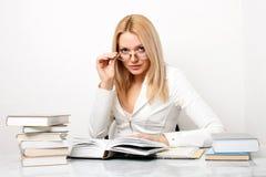 Vidros desgastando da mulher nova na tabela com livros Fotografia de Stock