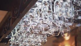 Vidros diferentes que penduram de um suporte dos produtos vidreiros acima do contador da barra video estoque