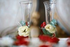 Vidros do casamento com laço, as flores brancas e as folhas do verde com fitas vermelhas Imagem de Stock