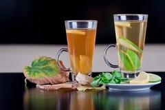 Vidros do chá na tabela de madeira com folhas de outono Imagem de Stock