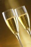 Vidros do champanhe com as nozes do fundo do ouro foto de stock