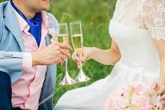 Vidros do champanhe da terra arrendada da noiva e do noivo Fotografia de Stock