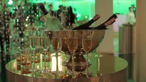 Vidros do champanhe e do vinho na tabela de bufete, em uma garrafa do champanhe ou no vinho em uma cubeta em um fundo dos povos vídeos de arquivo