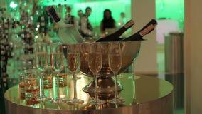 Vidros do champanhe e do vinho na tabela de bufete, em uma garrafa do champanhe ou no vinho em uma cubeta em um fundo dos povos filme