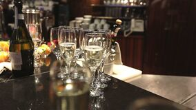 Vidros do champanhe e do vinho na tabela de bufete, em uma garrafa do champanhe ou no vinho em uma cubeta em um fundo dos povos video estoque