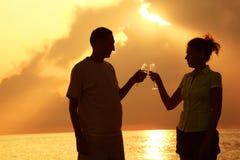 Vidros do clink do homem e da mulher. Noite do verão. Imagens de Stock Royalty Free