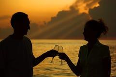 Vidros do clink do homem e da mulher. Silhuetas no mar Fotos de Stock Royalty Free
