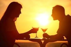 Vidros do clink dos pares no por do sol fora Imagens de Stock Royalty Free
