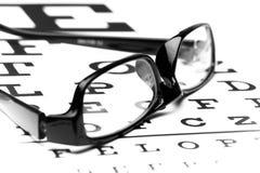 Vidros do olho que encontram-se na carta de Snellen foto de stock