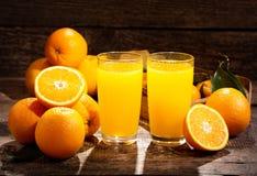 Vidros do suco de laranja com frutos frescos Foto de Stock