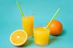 Vidros do suco de laranja com palha e das fatias no fundo brilhante Fotos de Stock