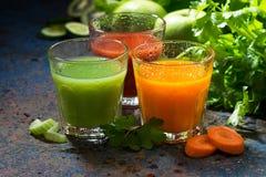 Vidros do suco fresco do aipo e das cenouras na tabela escura Fotos de Stock
