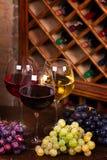 Vidros do vinho do vermelho, o cor-de-rosa e o branco com queijo, e uva na adega de vinho Imagens de Stock