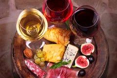 Vidros do vinho do vermelho, o cor-de-rosa e o branco com uva, figos e nozes na adega de vinho Fotos de Stock Royalty Free