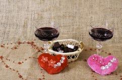 Vidros do vinho, dos dois corações e de uma cesta com chocolate Fotografia de Stock