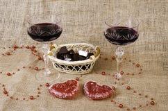 Vidros do vinho, dos dois corações e de uma cesta com chocolate Imagens de Stock