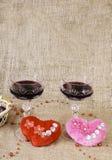 Vidros do vinho, dos dois corações e de uma cesta com chocolate Imagem de Stock Royalty Free