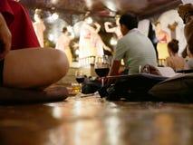Vidros do vinho no assoalho de assento no meados de dos turistas que vêm apreciar o desempenho e o ruído tailandeses do norte tra imagem de stock