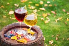 Vidros do vinho vermelho e branco com a uva no tambor de vinho velho fora Fotografia de Stock Royalty Free