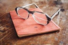 Vidros do vintage no livro velho imagens de stock royalty free