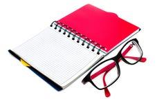 Vidros e caderno isolados no branco Fotografia de Stock Royalty Free