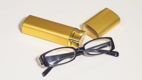 Vidros e caixa pretos elegantes do ouro para eles Imagens de Stock