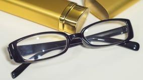 Vidros e caixa pretos elegantes do ouro para eles close-up Fotografia de Stock Royalty Free