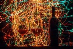 Vidros e garrafa de vinho no fundo e em fugas pretos Imagens de Stock